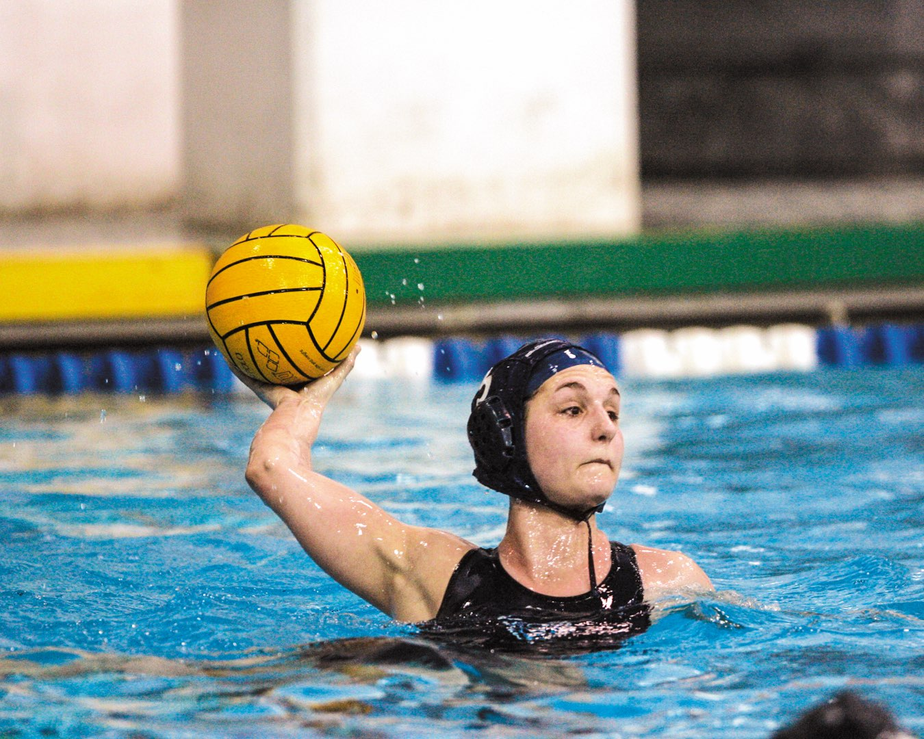Villanova Women's Water Polo player in her swim in the pool about to launch the bright yellow water polo ball