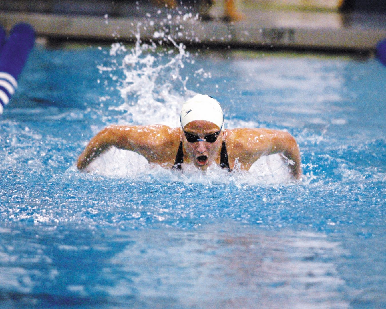 Water ripples behind a Villanova Women's Swimming and Diving team member in her cap and goggles, as she speeds down the lane