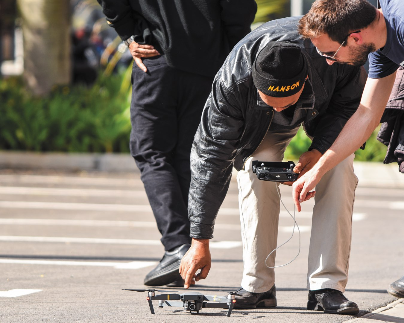 In a parking lot in Madagascar, a CRS staff person bends over a drone as Eric Wagner trains him to launch it