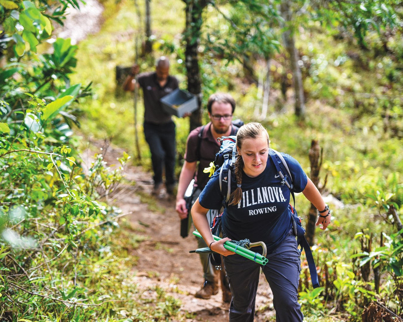Female student in a Villanova T-shirt carrying water testing equipment and male student walk on a dirt path in Madagascar