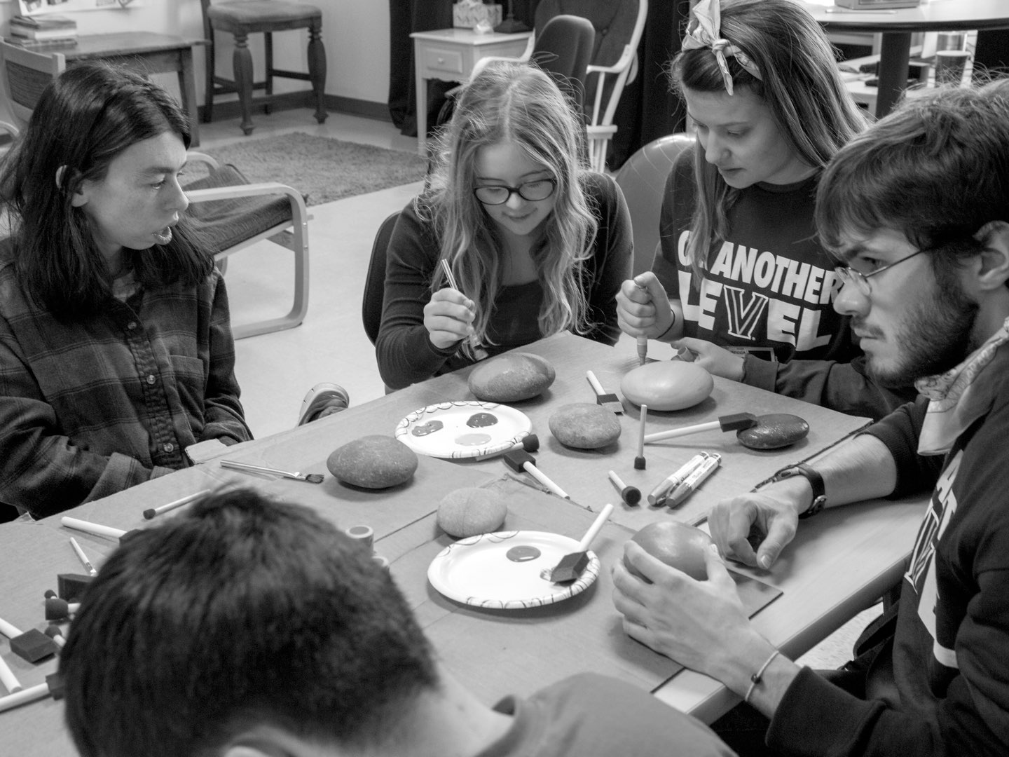 Black-and-white photo of Villanova's LEVEL students painting rocks with students from the Community School of Davidson.