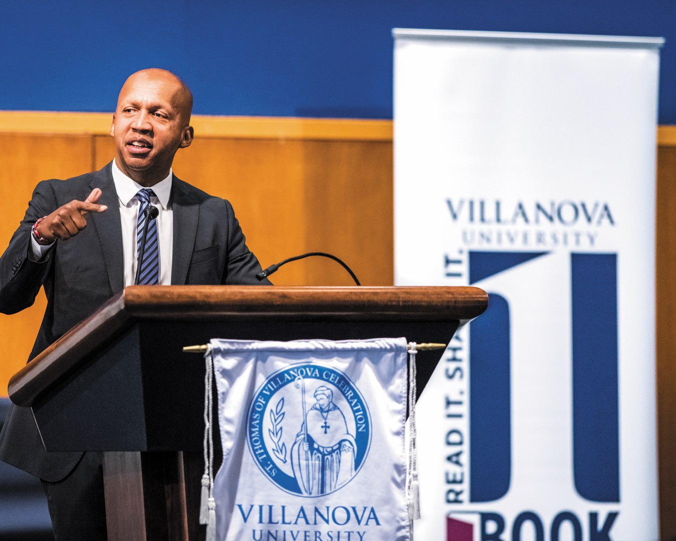 Adela Dwyer-St. Thomas of Villanova Peace Award recipient Bryan Stevenson in a suit speaking at a podium