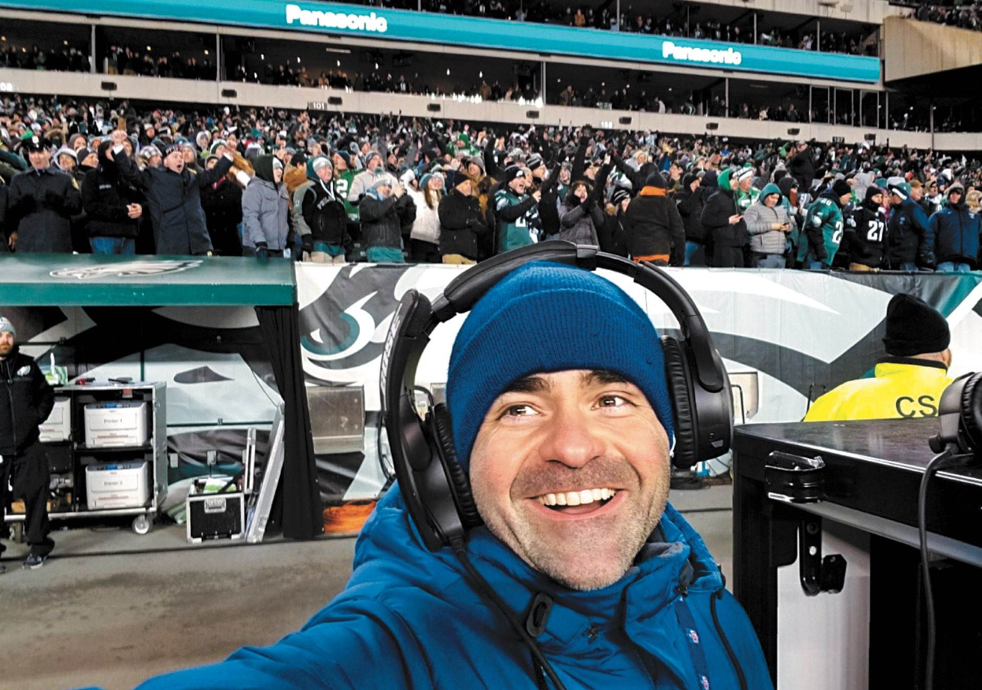 A selfie of CPS alumnus Ron Tedesco smiling in headphones on the sidelines with packed stands of Eagles fans behind him