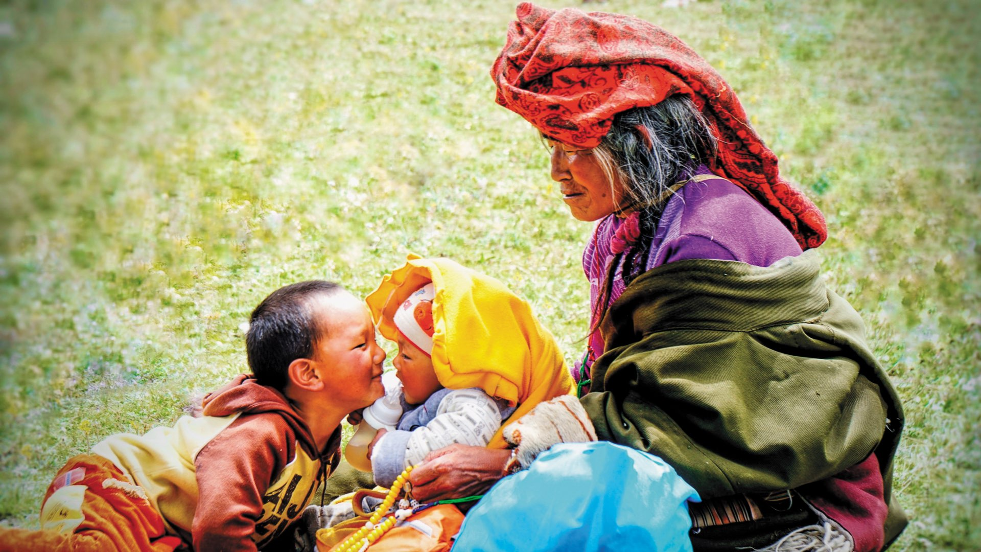 An elderly Mongolian woman holding a young baby face to face with a young Mongolian boy on the grass in vivid clothing