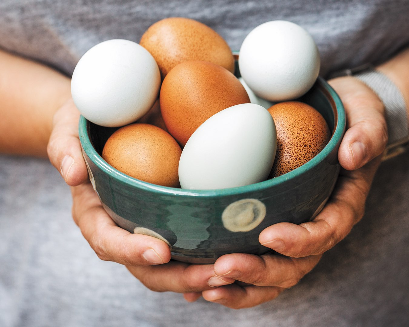 Hands holding a bowl full of brown and white eggs