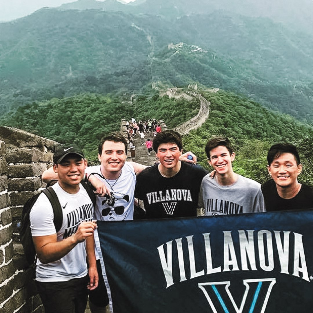 Five male Villanova students in Villanova T-shirts holding a Villanova banner in front of the Great Wall of China
