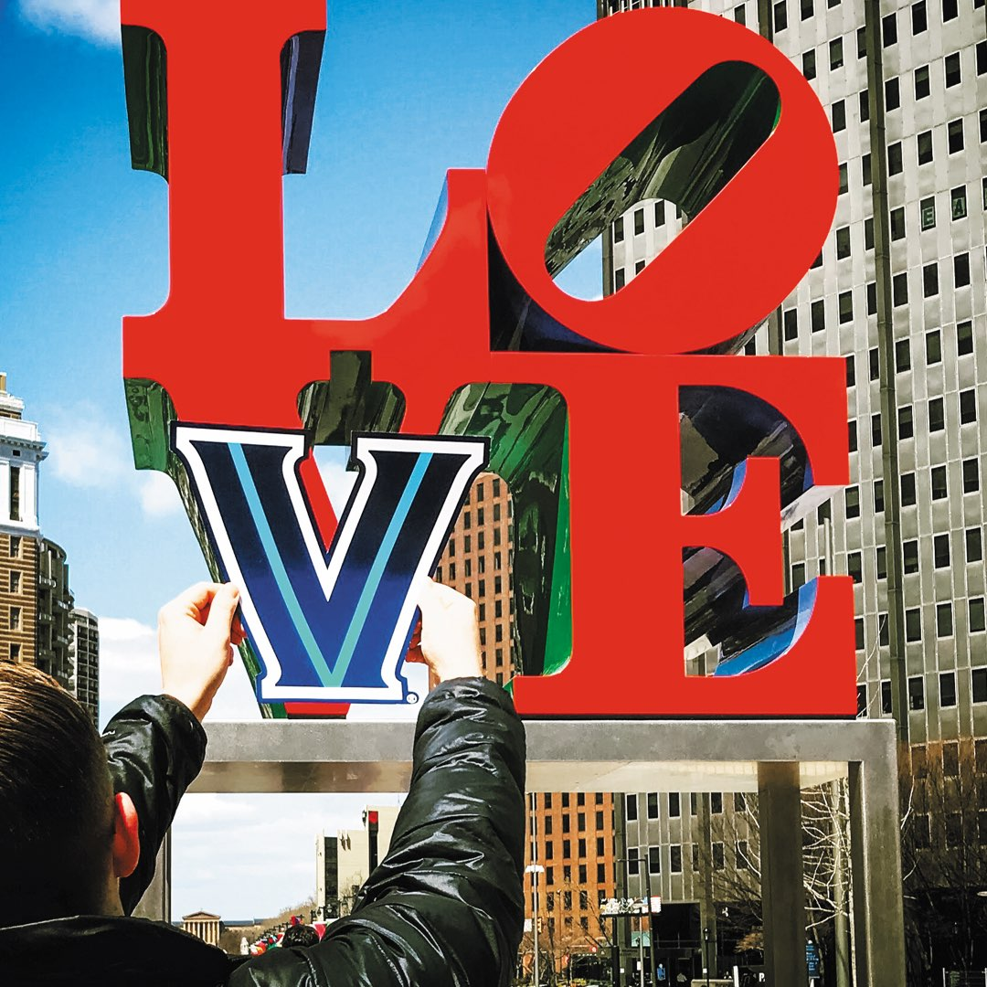 A student holding up a Villanova V over the V on the iconic Love statue in Philadelphia