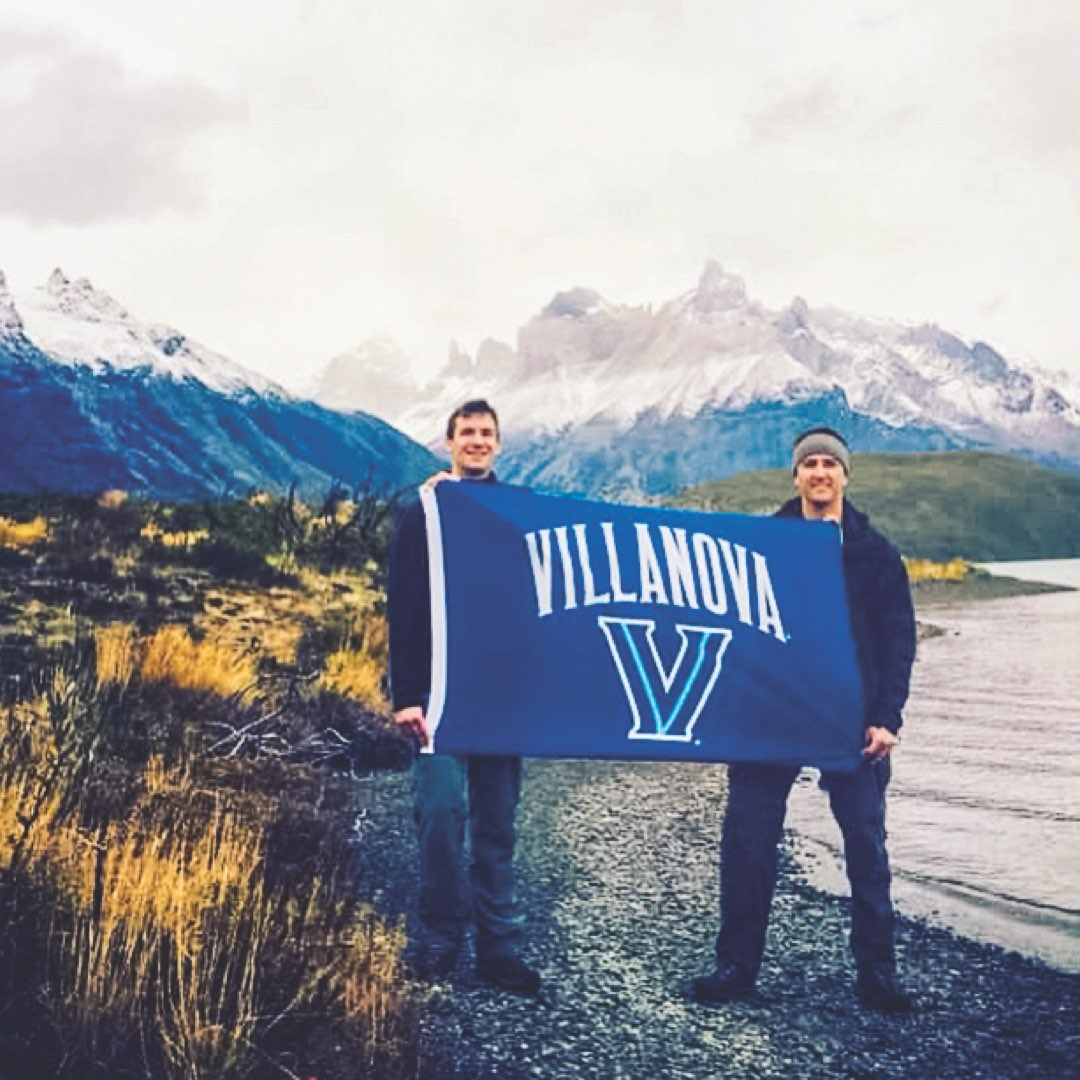Two male Villanova alumni holding a Villanova banner in Torres del Paine National Park, Chile