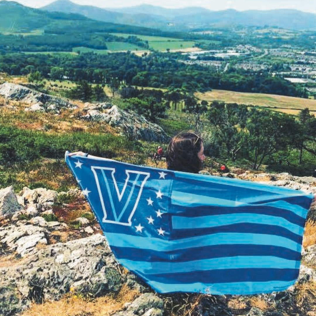 A female Villanova student holding an American flag Villanova banner in front of the green hills of Bray, Co. Wicklow in Ireland