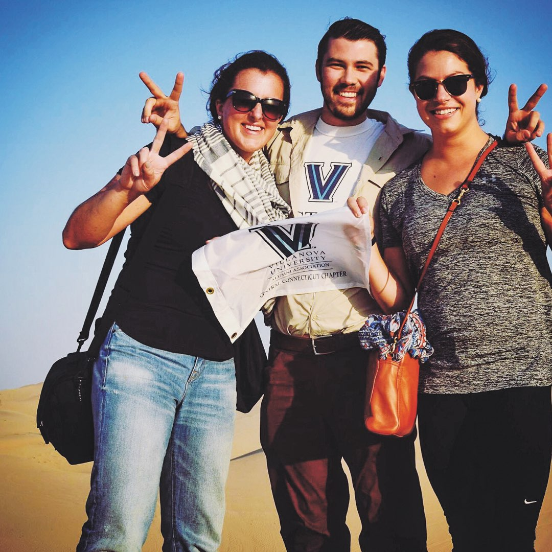 A group of three Villanova alumni holding a small white Villanova flag in the desert of Abu Dhabi, United Arab Emirates
