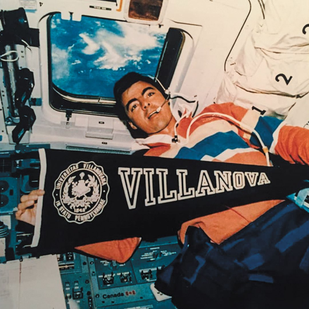 Astronaut and Villanova alumnus Andy Allen holding a Villanova pendant inside a NASA Space Shuttle in outer space in 1992