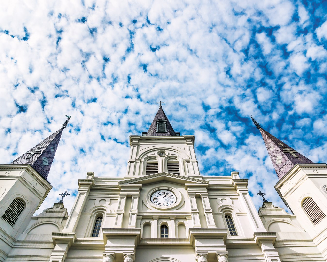 Close-up of the iconic clock tower of Saint Louis Cathedral in New Orleans, Louisiana against a bright blue sky