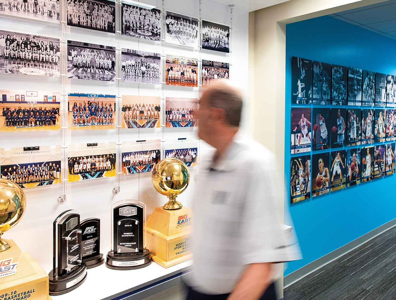 Harry Perretta walks through a hallway of trophies and team photos in Finneran Pavilion