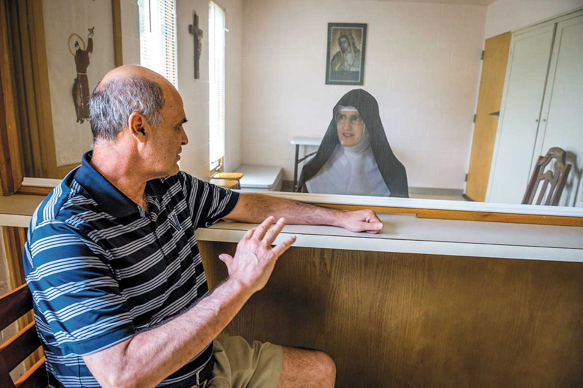 Sister Rose Marie, wearing her full religious habit, has a visit with Harry Perretta through a transparent screen