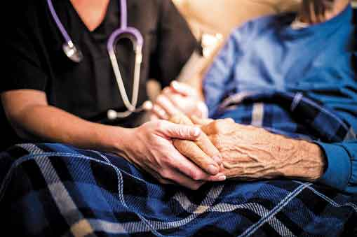 Health care worker's hands holding an elderly person's hands