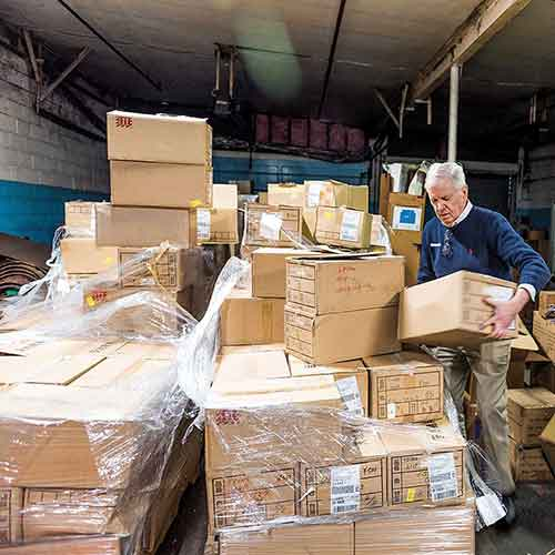 1983 Tom Costello Jr. in a room full of boxes of socks