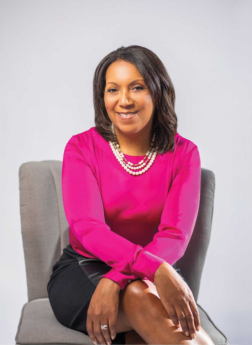 Kimberly Kersey sitting on a desk chair in a bright pink sweater