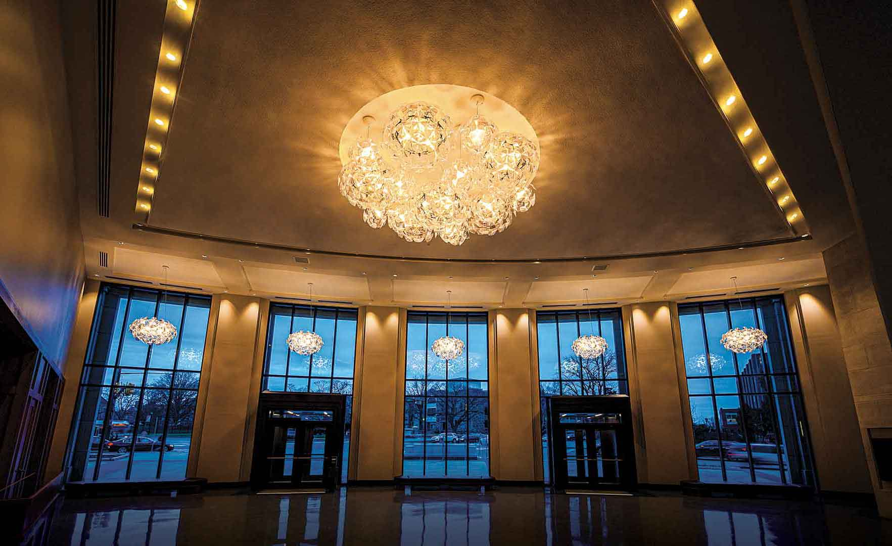 The performing arts center lobby, with a wall of windows looking out on Lancaster Ave and elegant, striking light fixtures