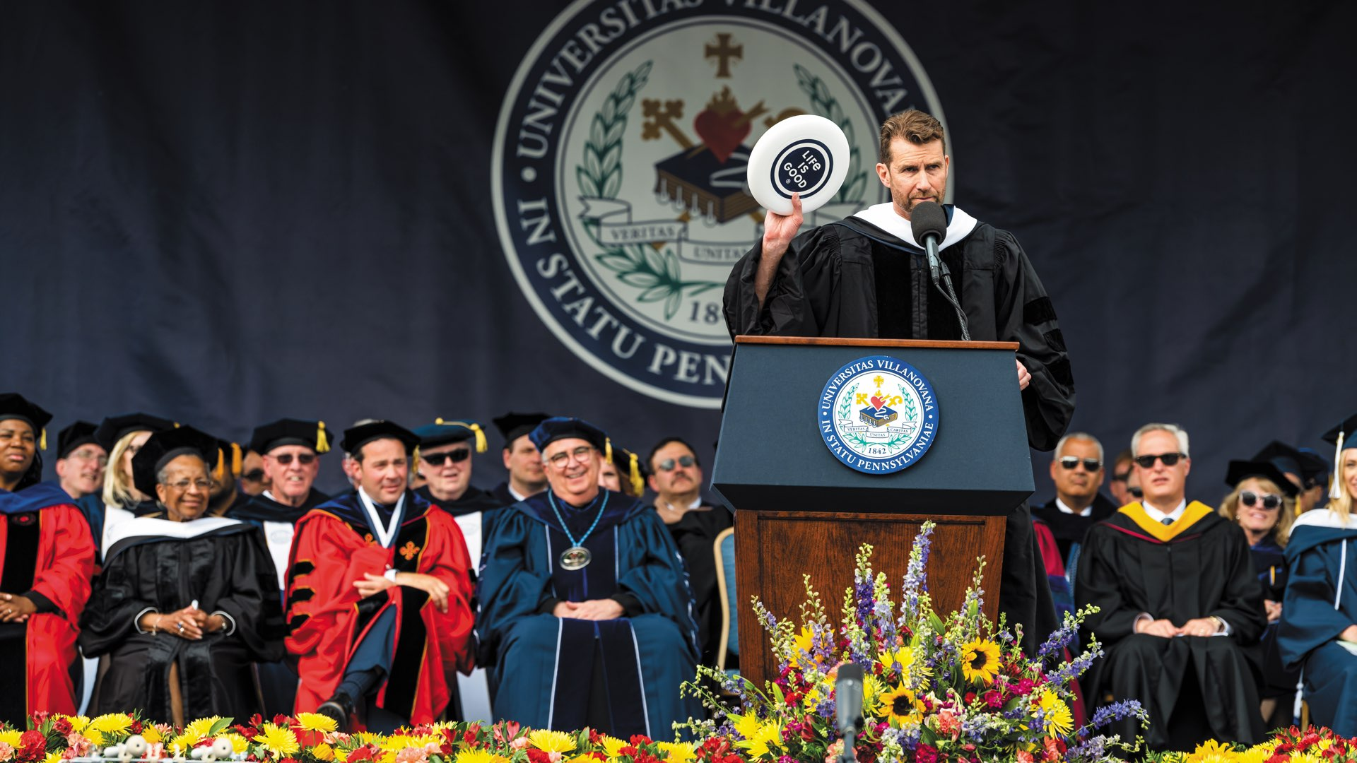 On stage, Commencement speaker Bert Jacobs at the podium in graduation regalia holding up a Life Is Good frisbee