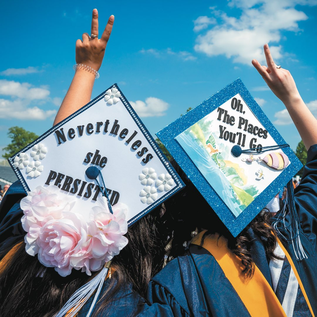 "Two female students giving the peace sign, wearing caps that read ""Nevertheless she persisted"" and ""Oh the places you'll go"""
