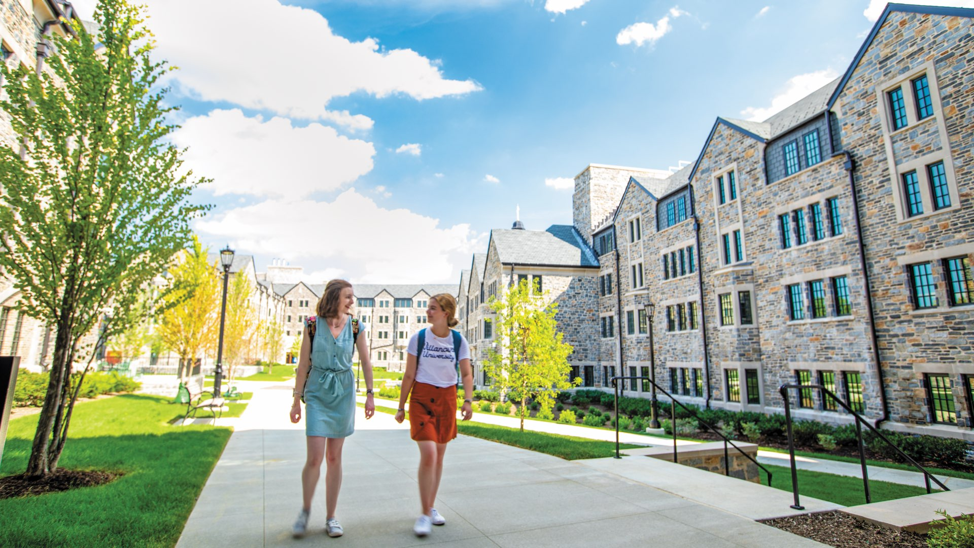 Two female students in backpacks walking through The Commons on a bright sunny day