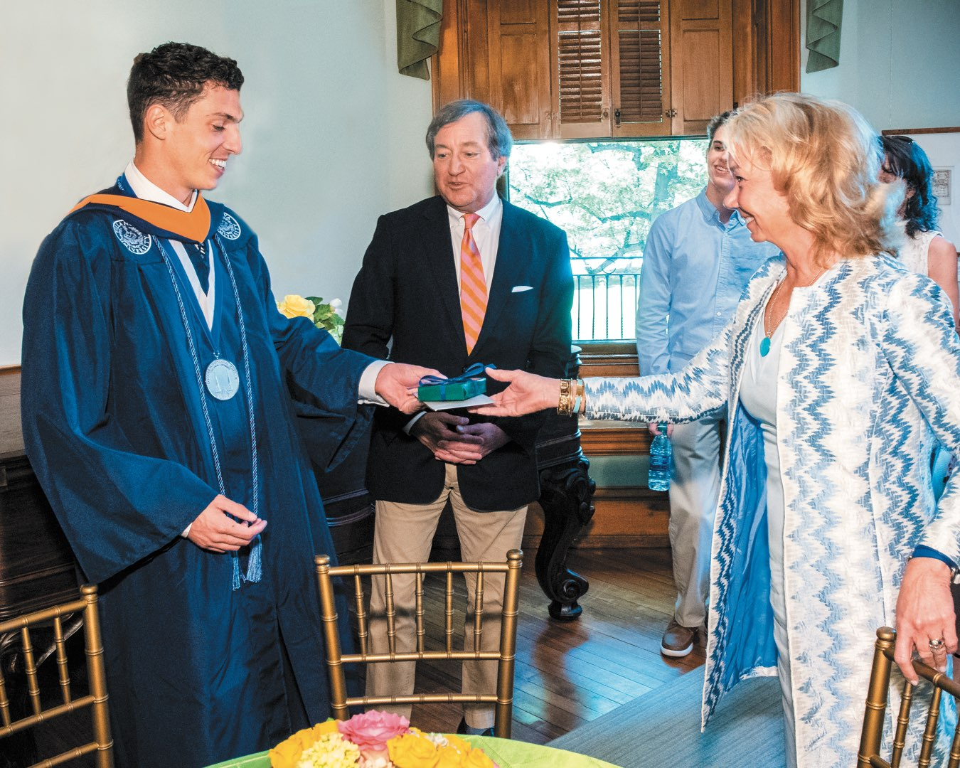Wearing his regalia, Alex Alberi receives a graduation gift from Polly and Terry O'Toole