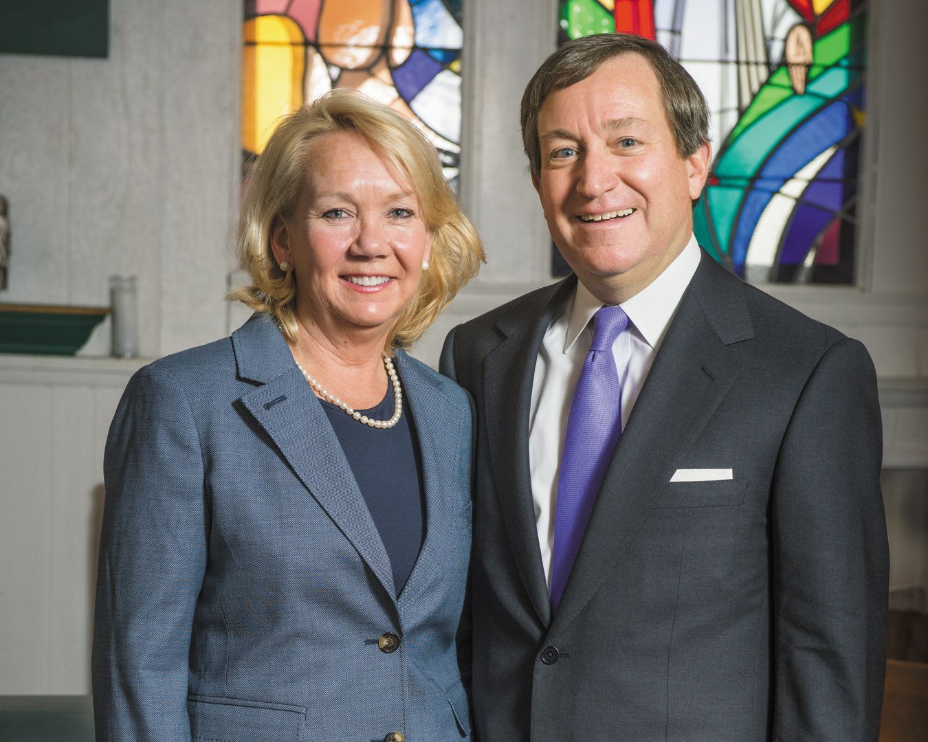 Polly and Terry O'Toole smiling in front of stained glass windows in the chapel