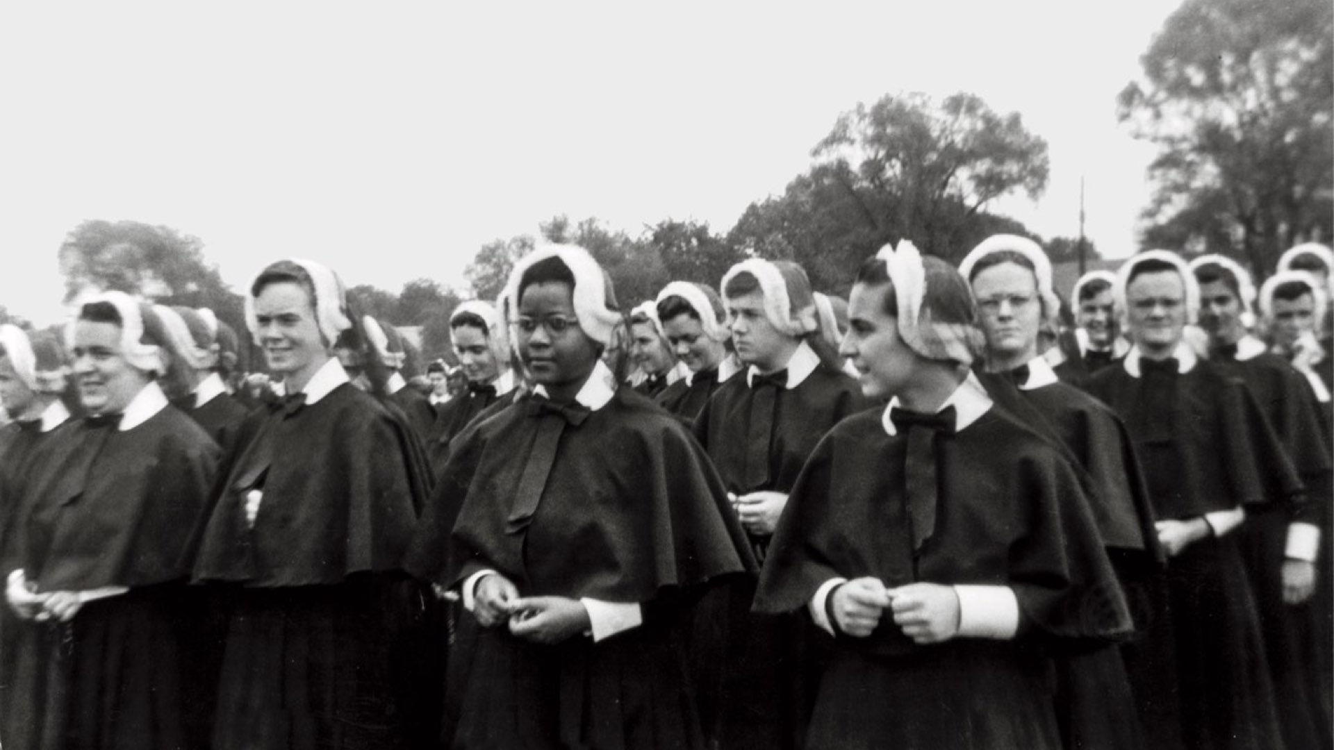 A black-and-white photo of a young Sister Cora Billings in habit amid a large crowd of novitiate nuns