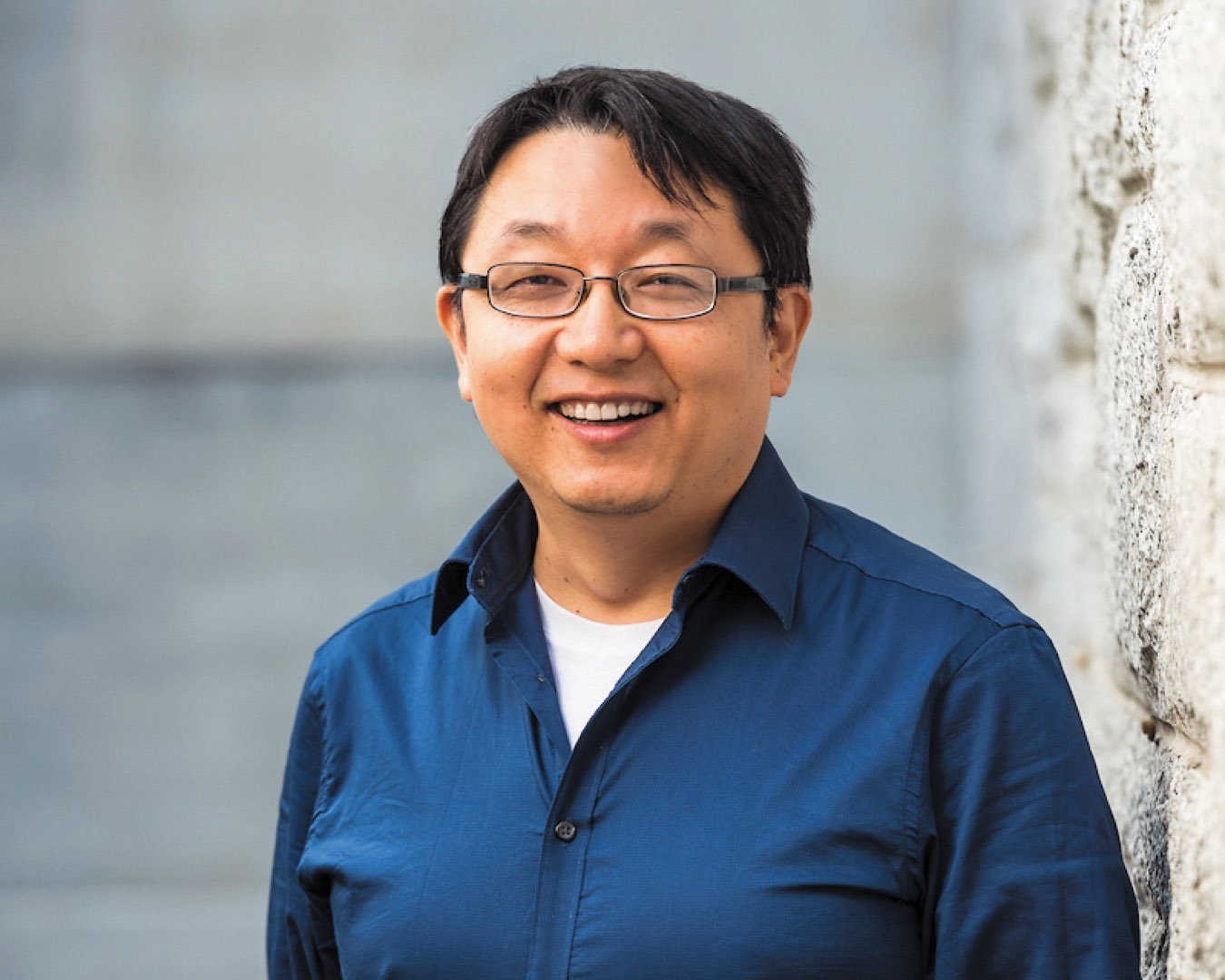 Headshot of Dr. Qianhong Wu wearing glasses and a blue dress shirt unbuttoned, smiling