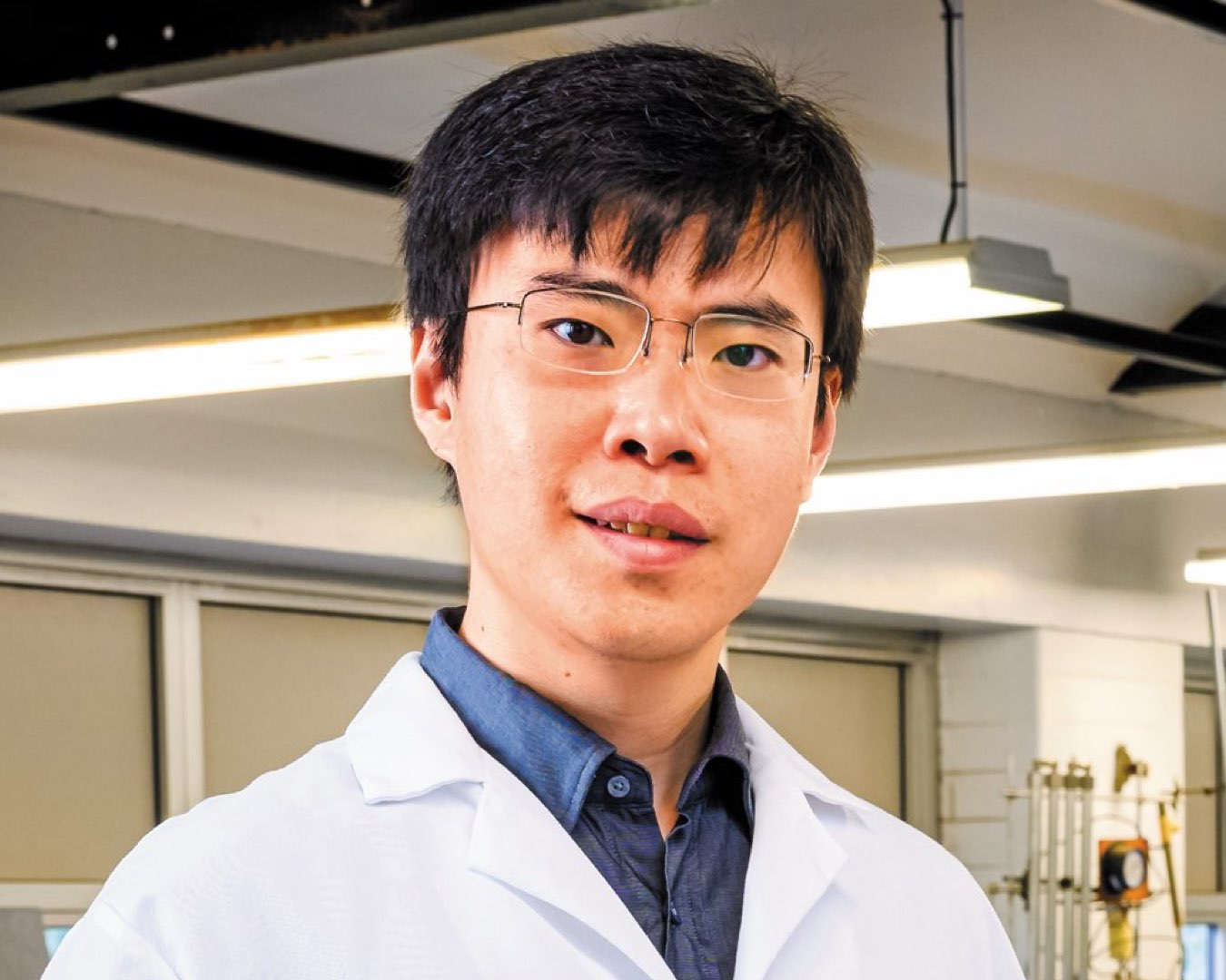 Headshot of PhD student Ji Lang wearing glasses in a white lab coat
