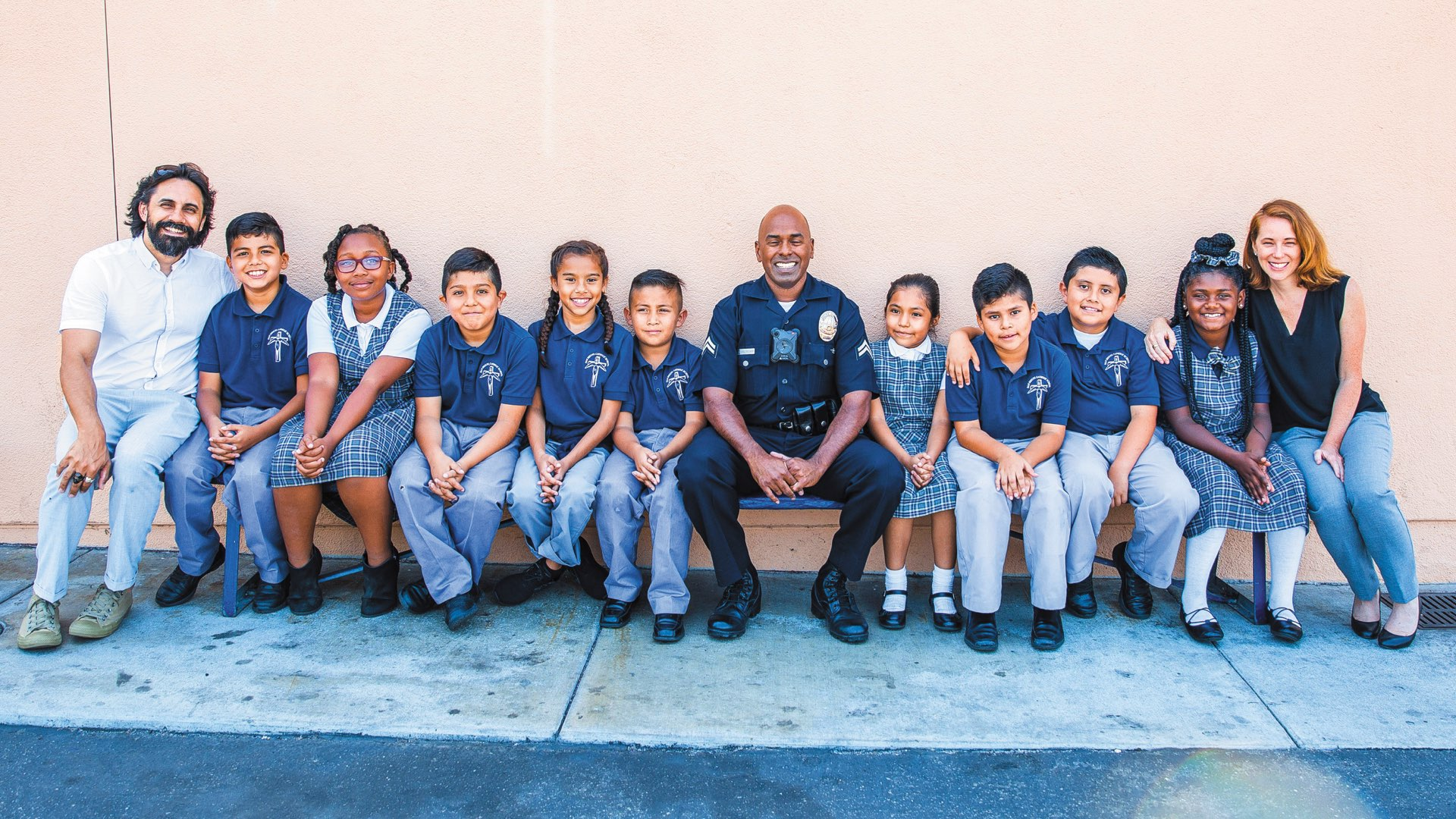 2003 Liberal Arts and Sciences alumna Theresa Gartland sitting on a bench with a group of schoolchildren and a police officer