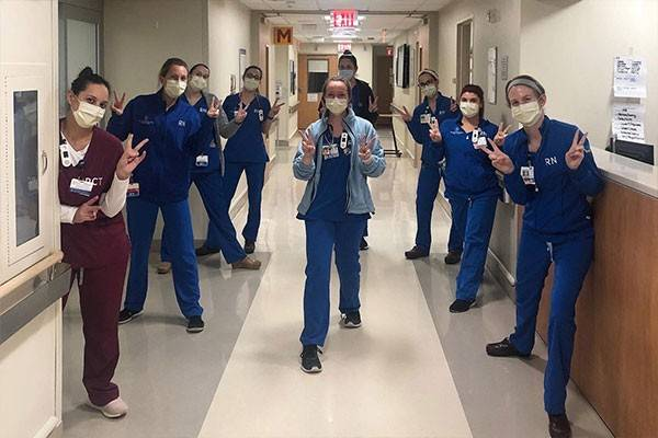 Doctors and Nurses lined up in hostial hallway giving V's up
