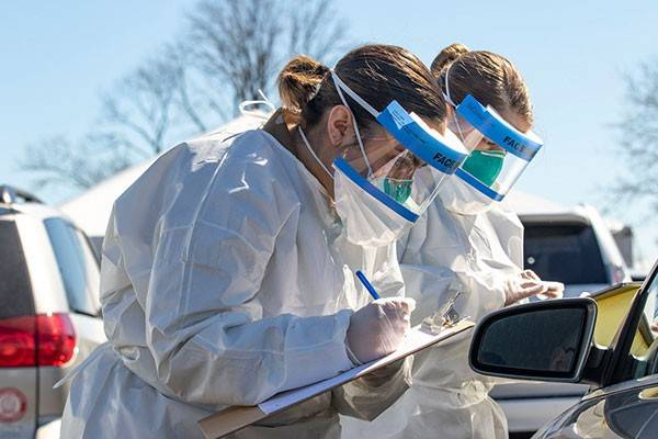 Two nurses with masks write on clipboards