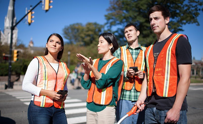 Associate Professor Seri Park, who focuses on transportation engineering, stands with three students in orange vests observing a main intersection on Villanova's campus.