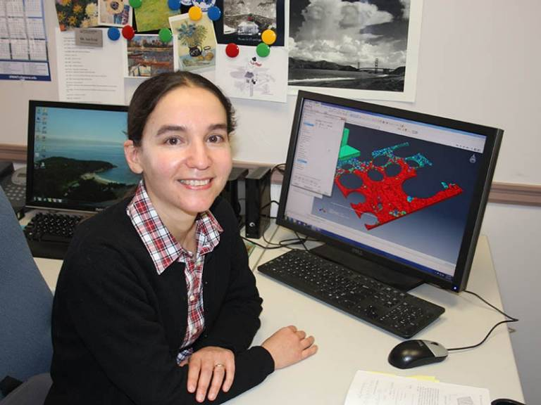 Associate Professor Ani Ural sits at her desk with her computer showing a modeling program.