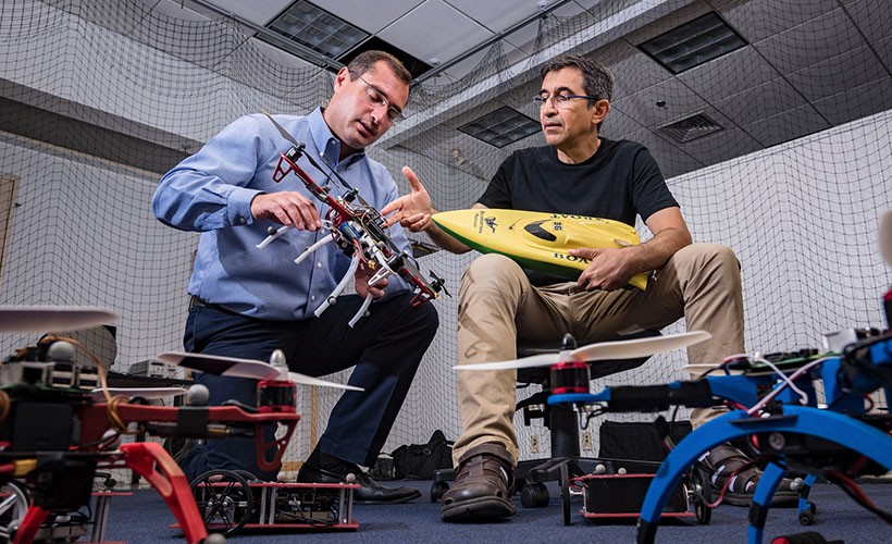 Sergey Nersesov, PhD, and Hashem Ashrafiuon, PhD, in the lab with autonomous vehicles.