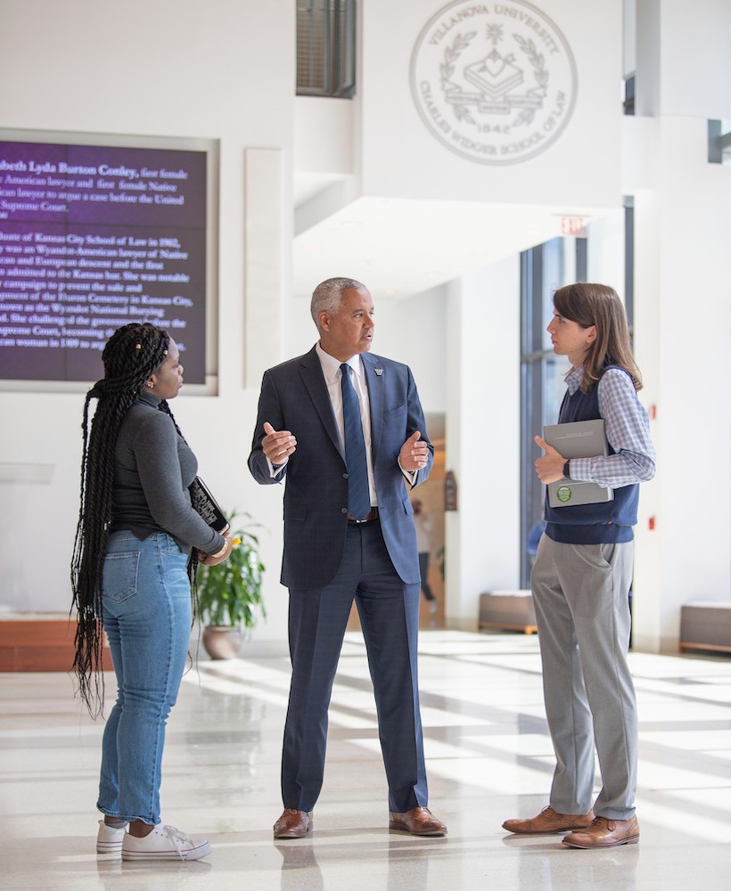 Mark Alexander, Dean of Villanova's Law School, stands in the Law School Commons talking with two students.