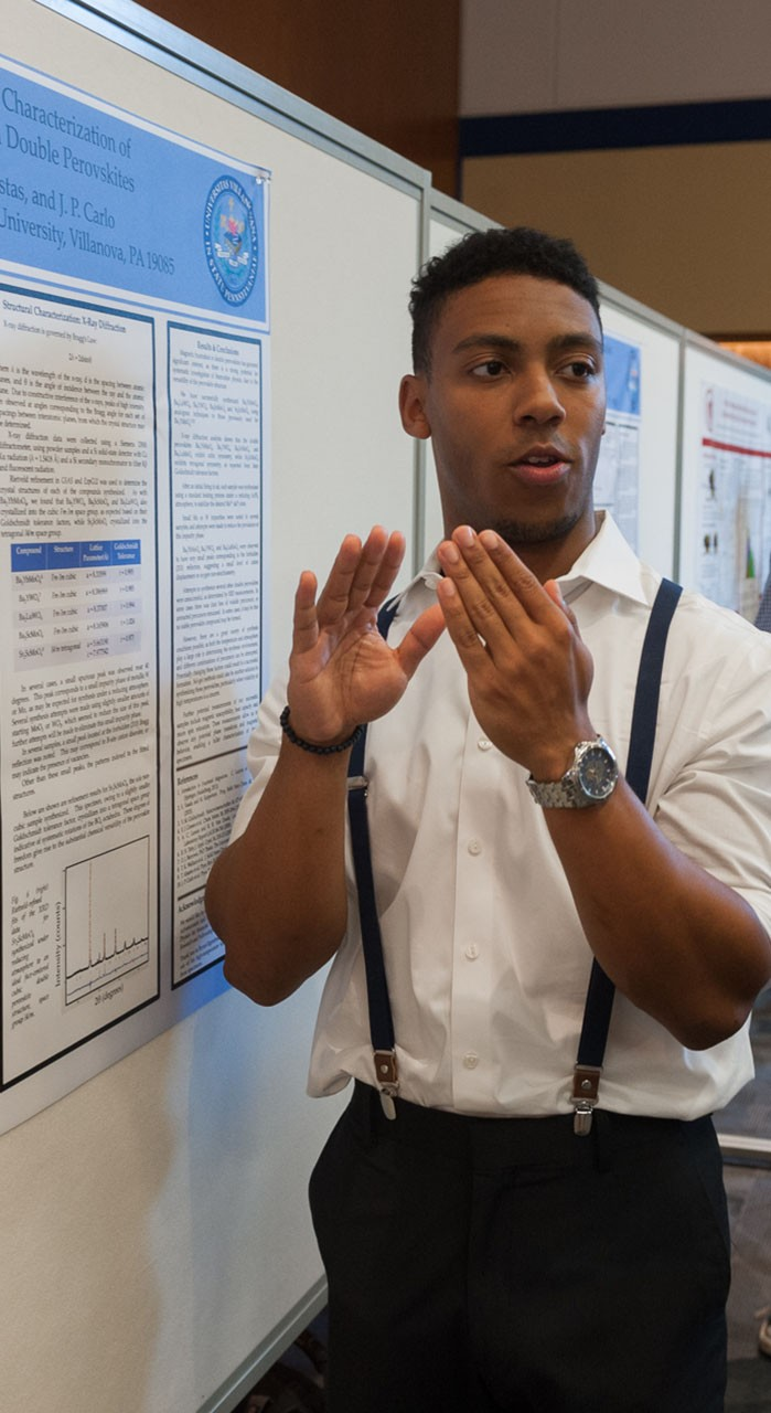 A student presents his findings at an undergraduate research poster session.