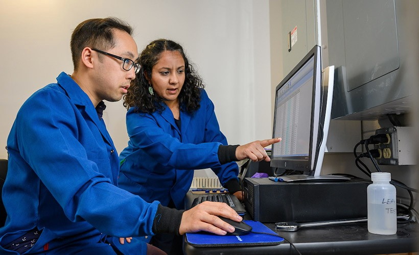 A professor and student work together at a computer.
