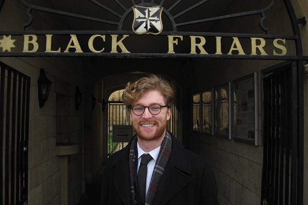 Student stands outside a Blackfriars sign in Oxford.