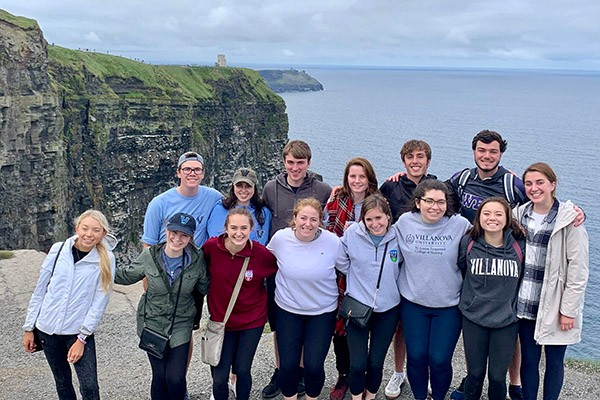 Villanova students pose for a photo by the cliffs of Ireland's coastline.