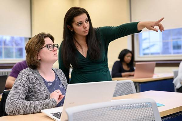 Teena M. Amador, Esq, works one-on-one with a student in Villanova's Paralegal program.