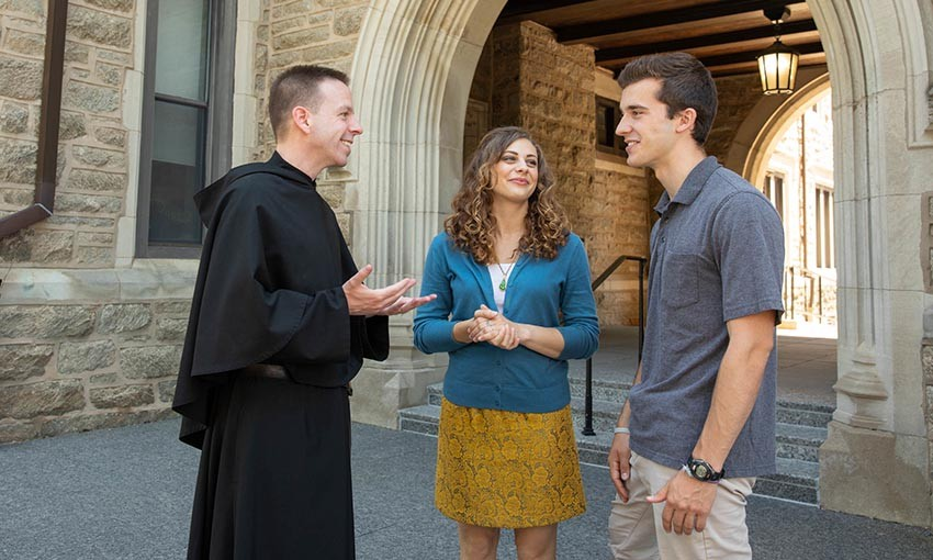 Rev. Kevin DiPrinzio OSA, talking with students outside Corr Hall on the Villanova University campus.