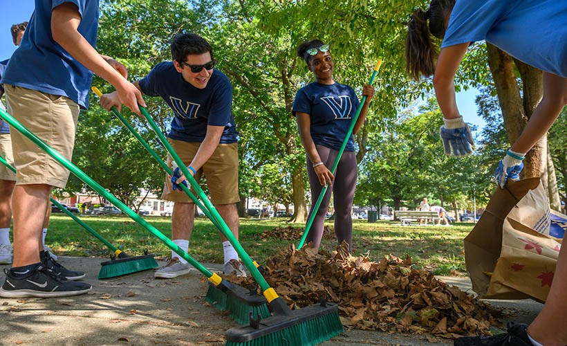 A group of four students in Villanova shirts doing service work with landscaping