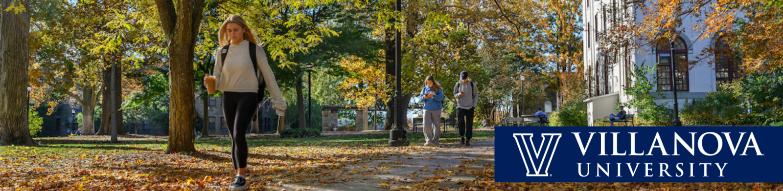Header with students walking through autumn leaves