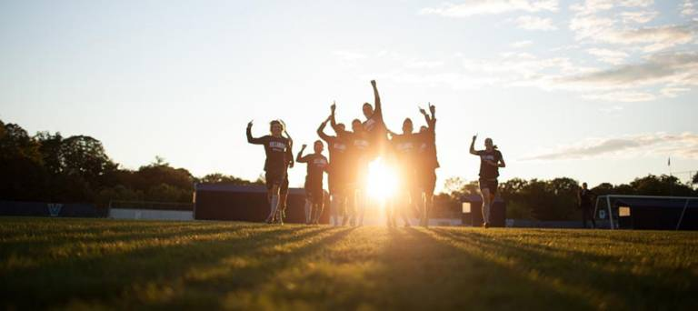 image showing students on a soccer field as the sun sets