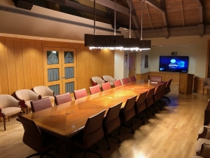 Conference room with a single conference table that can seat about sixteen people, and a TV at the far end