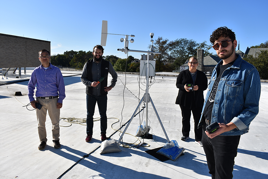 Members of the Environmental Science research team stand with their air pollution monitoring equipment.