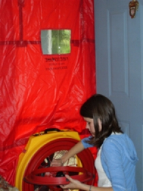 Graduate student Sarah Barnett uses a blower door to measure airtightness.