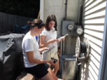 Barnett and Margaret Tsudis ChE '10 install a meter that provides real-time feedback on energy consumption.